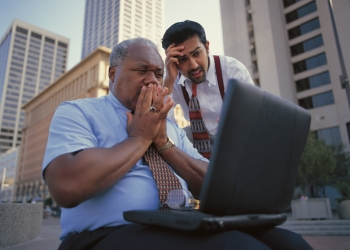 close-up of two businessmen shocked at the data on a laptop screen